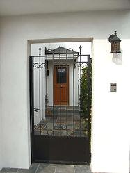 輸入住宅/住宅施工事例/白の左官壁に映えるアイアンの門扉。