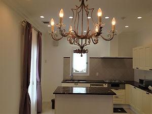 輸入住宅/住宅施工事例/クリーム色のキャビネットが温かみあるキッチン。アンティークな印象の照明がアクセント。