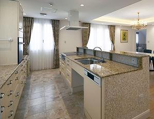輸入住宅/住宅施工事例/茶系の御影石の天板、モザイク大理石が明るいキッチン。キャビネットは収納力抜群。