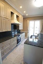 輸入住宅/住宅施工事例/カプチーノ色の無垢扉材、御影石のカウンターのアイランドキッチン。