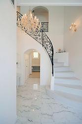 輸入住宅/住宅施工事例/緩やかなカーブラインの階段。階段下の開口から、キッチン、洗面、浴室に繋がるプラン。