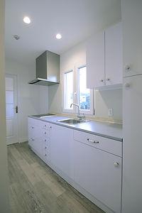 住宅施工事例。フランス製のオーダーキッチンは鏡面仕上げの白い扉にフランスらしい陶器のつまみ。