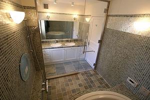 住宅施工事例。洗面コーナーとバスルームは強化ガラスで間仕切ることで一体になった自慢の一室。