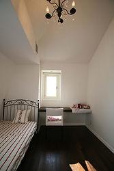 輸入住宅/住宅施工事例/マンサール屋根のドーマー窓と屋根形状になった勾配天井が特徴の寝室。