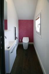 輸入住宅/住宅施工事例/シンプルながらもピンクの壁が印象的なトイレ。