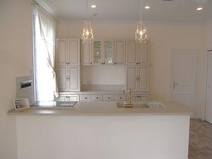 輸入住宅/住宅施工事例/淡いトーンのアイランドキッチン。壁抜きのレンジフードが無機質な存在感を消してくれる。