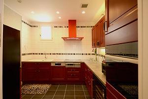 輸入住宅/住宅施工事例/ボルドーがかった赤のフランス製キャビネットに合わせてレンジフードも赤を選択。