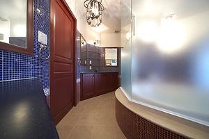 住宅施工事例。深い赤と青のガラスモザイクを2色使いした洗面。洗面家具は日本の職人が作ったもの。