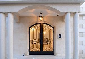 住宅施工事例。アイアン扉のエントランス。 エントランスの両側には光を取り入れながら設備を収容する中庭があります。