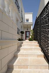 輸入住宅/住宅施工事例/ロートアイアンのフェンスと重厚な大理石 トラバーチンのステップが美しい。