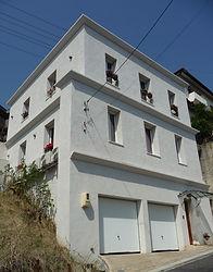 輸入住宅/住宅施工事例/漆喰壁と窓辺に飾られた花のある邸宅