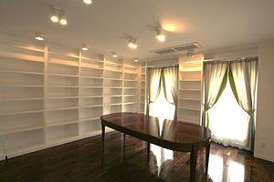 輸入住宅/住宅施工事例/壁一面に本棚を設置した家族部屋。ウォールナットの床には高級感ある光沢のコーティング。