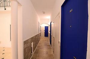 住宅施工事例。廊下を歩くと部屋の玄関に。玄関扉はフランスらしいブルーのカラー。