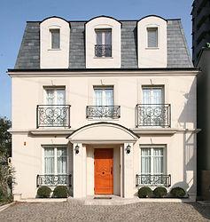 輸入住宅/住宅施工事例/シンメトリーの安定感ある外観。外壁は重厚感あるライムストーン、屋根は玄昌石を採用。