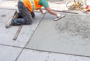 Spreading concrete for sidewalk repair.j