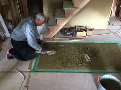 左官工事。薪ストーブの床と玄関洗い出し