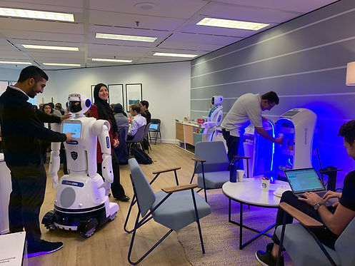 People mingling and interacting with service robots in professional community space.