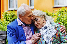 elderly couple sitting on park bench together looking sad