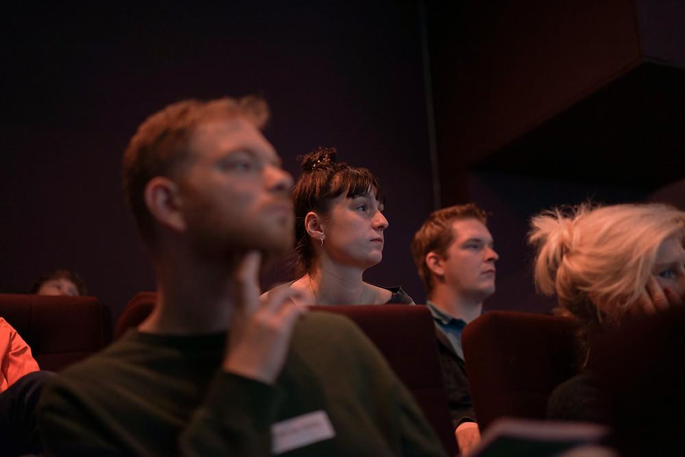 Een foto van een theaterzaal. Op de foto zie je een groepje mensen die gefocust aan het kijken zijn.