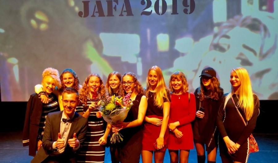 Een foto van een groep leerlingen die aan het poseren zijn voor een foto. De leerlingen staan op het podium voor een projectiescherm. Een meisje in het midden heeft een bos bloemen in haar hand.
