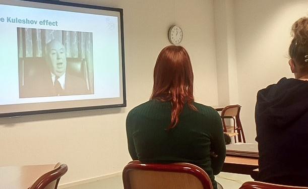Foto van twee studenten die naar een projectiescherm zitten te kijken. Op het projectiescherm is een foto van het Kuleshov effect te zien.