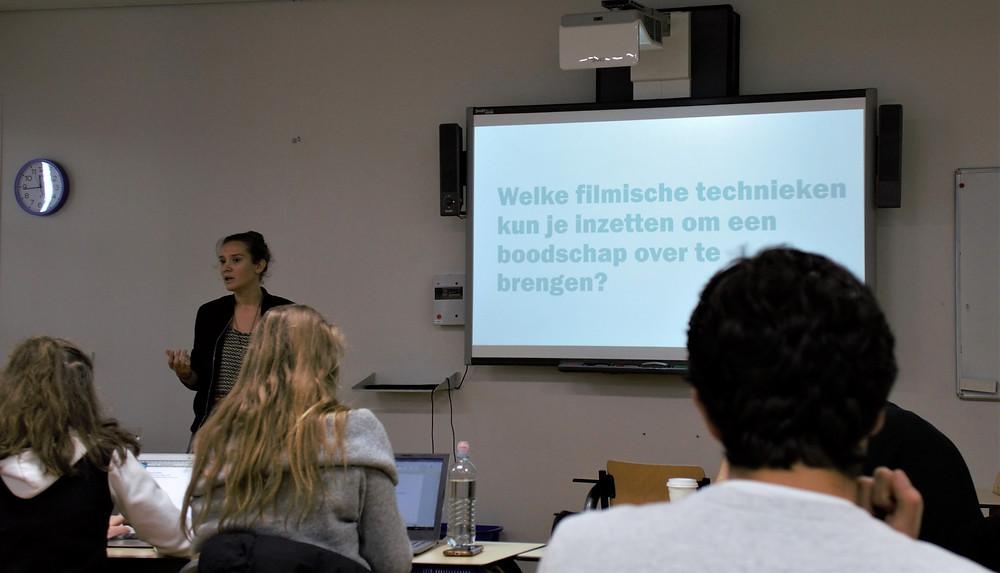 Een foto van een gastdocent die en presentatie aan het houden is voor een projectiescherm. In de klas zitten studenten die naar de presentatie kijken.
