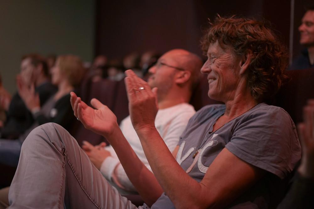 Een foto van het publiek in een theaterzaal. Vooraan op de foto zie je een man die met zijn handen aan het klappen is.