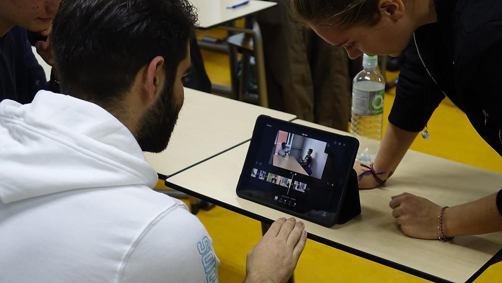 Een foto van een student en een gastdocent die aan het kijken zijn naar het scherm van een tablet. Op de tablet is een beeld te zien van twee mensen die met elkaar in gesprek zijn.