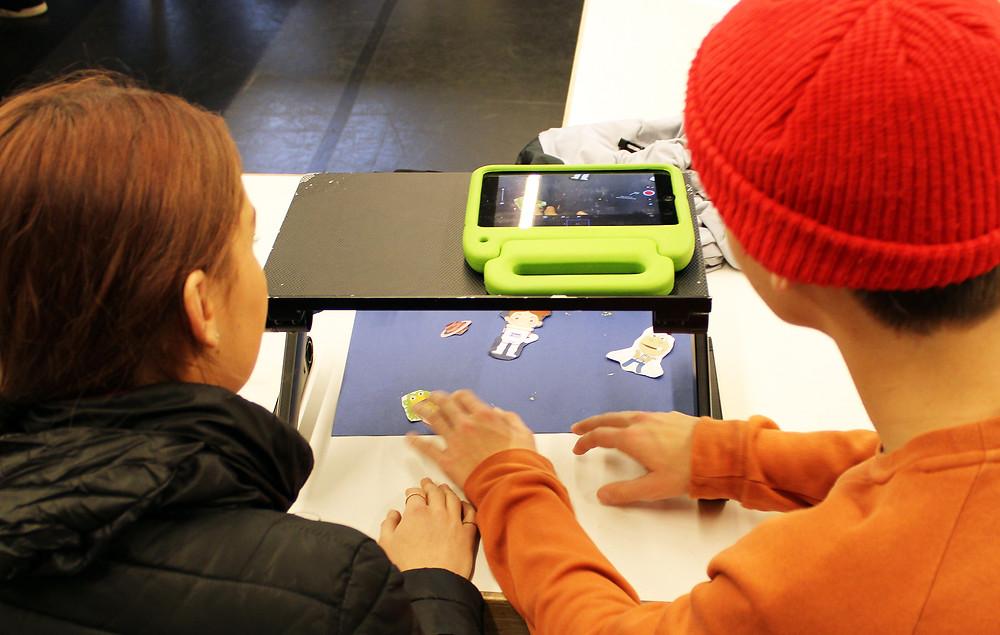 Een foto van twee leerlingen die foto's maken met een tablet. Ze maken foto's van een vel papier met daarop verschillende uitgeknipte animaties.