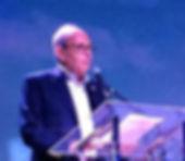 Tom Feltenstein speaking at podeum in Brazil