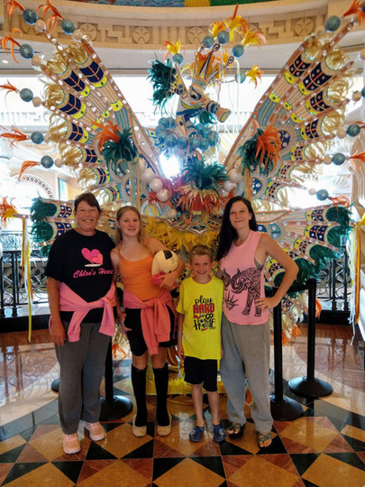 Chloe and family in front of a cool dragon sculpture.