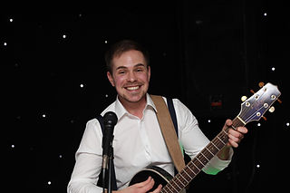 Male acoustic wedding guitarist. Happy faced and enjoying a fashionable local wedding.