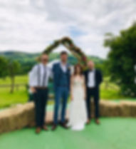A young newly married couple at the outside alter alongside their acoustic wedding band at a festival themed wedding at Barnutopia,  Wales. The band provided live music for their wedding ceremony, drinks reception and evening reception. This was a beautiful summer wedding.