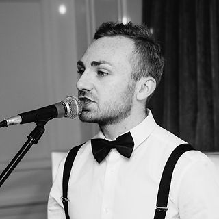 Male wedding singer. Singing into a microphone. Wearing a fashionable bowtie to fit in at a luxury wedding.