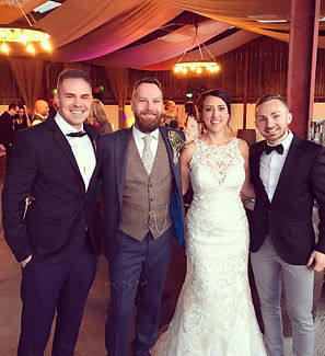 Formally dressed, an acoustic wedding band are pictured alongside a happy couple at rustic summer wedding in Shropshire. It was a beautiful barn wedding. The band provided live music performances and got the whole dancefloor rocking.