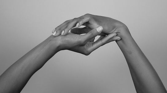B&W photo of two hands, one above the other, palms facing the other, with each hands' first and second fingers on the pulse point of the opposite hand.