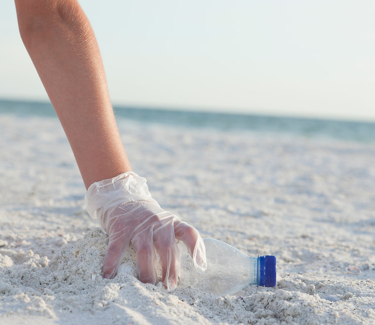 Beach Litter. Hand picking up discarded plastic water bottle.