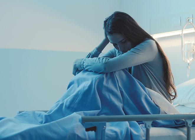 Sad female patient lying in the hospital