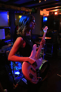 Laura Whiteman playing bass guitar in The Hit List