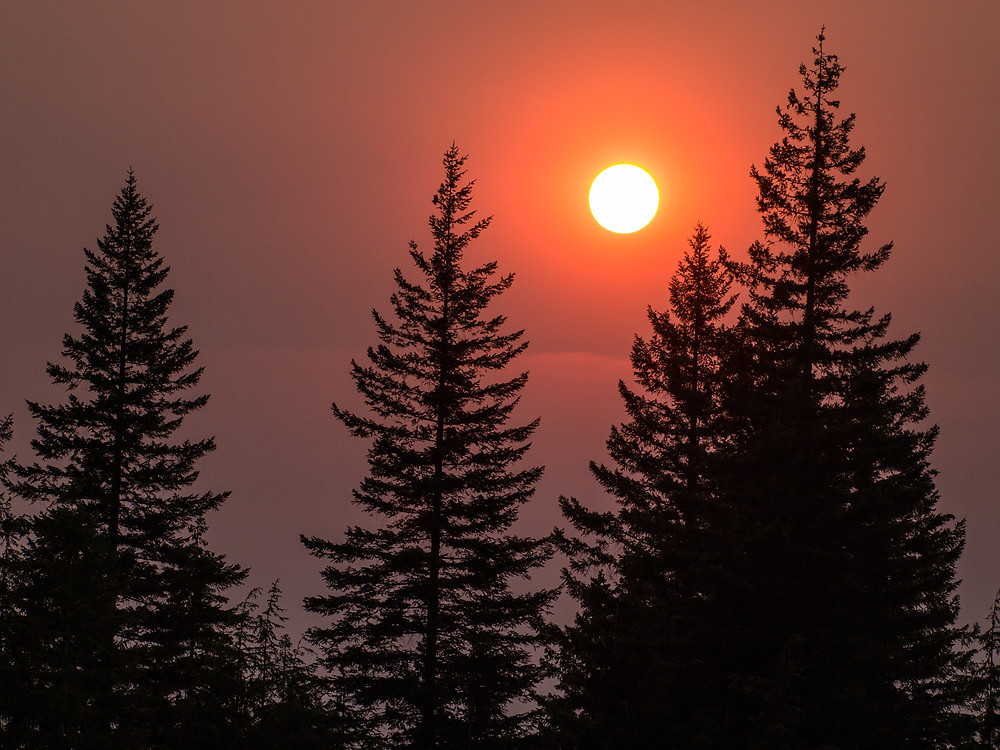 The sun sets as smoke reddens the sky over the Canadian wilderness