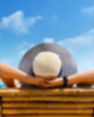 Woman in hat relaxing on beach, looking