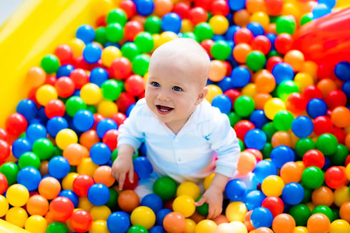 Happy laughing boy having fun in ball pi