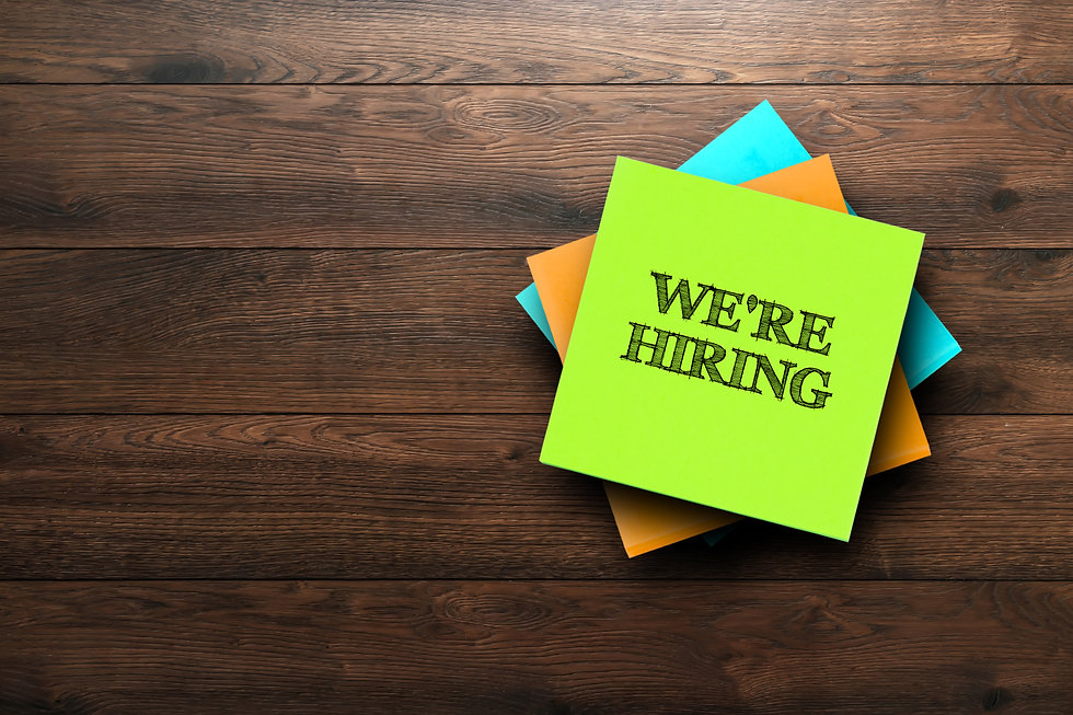 We're Hiring, the phrase is written on multi-colored stickers, on a brown wooden backgroun