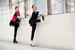 two-figure-skaters-stretching-legs-XYLGR