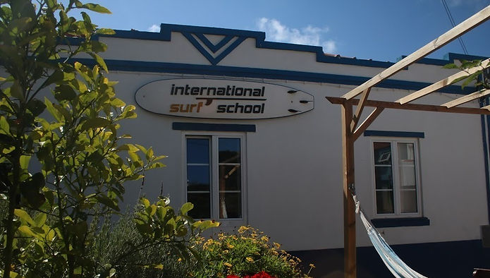 Intrnational Surf School Sagres Surfcamp main front with a surfboard on top gazebo and garden