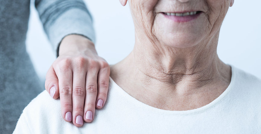 Elderly lady supported by carer