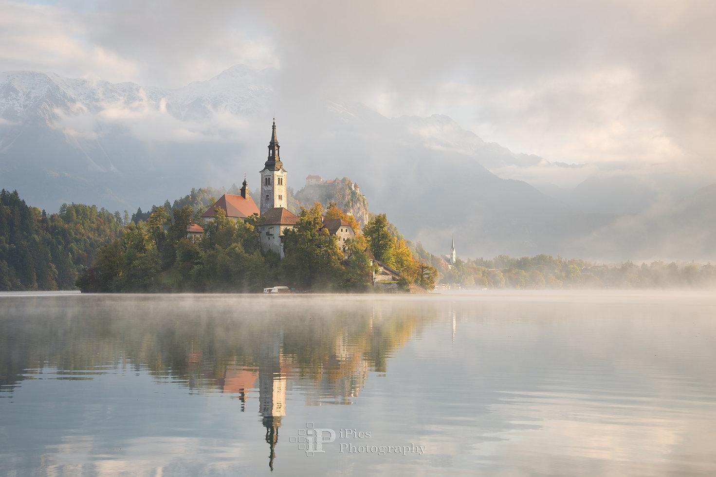 Landscape photograph of the church on the small island in Lake Bled and Bled Castle in the first sunlight of sunrise on a beautiful foggy morning in autumn with reflection in the calm water in Slovenia.