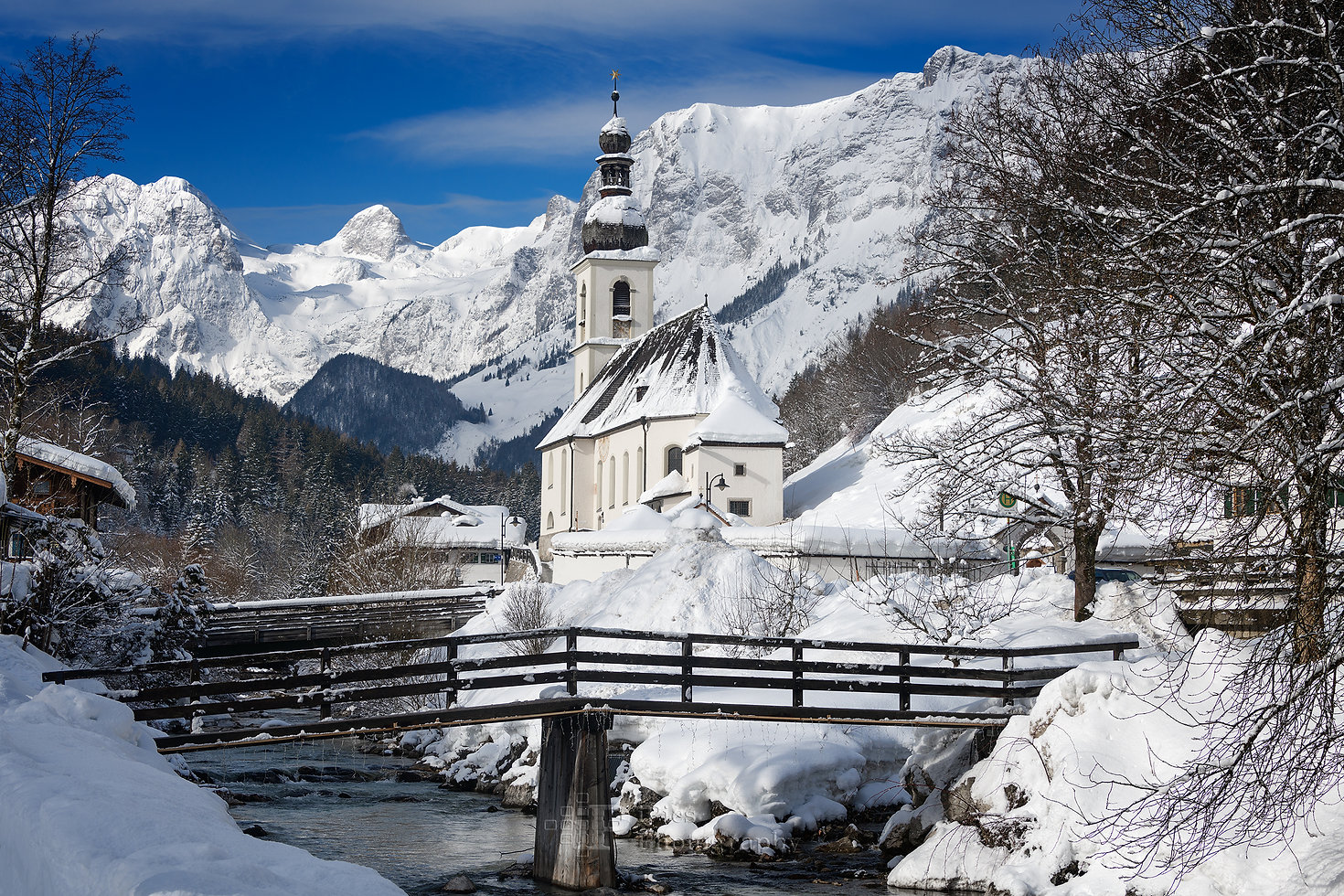 St. Sebastian church next to a mountain stream with a bridge and Reiter Alps mountains in the background, covered in snow under a blue sky, creating a winter wonderland landscape in Ramsau bei Berchtesgaden in Bavaria, Germany.