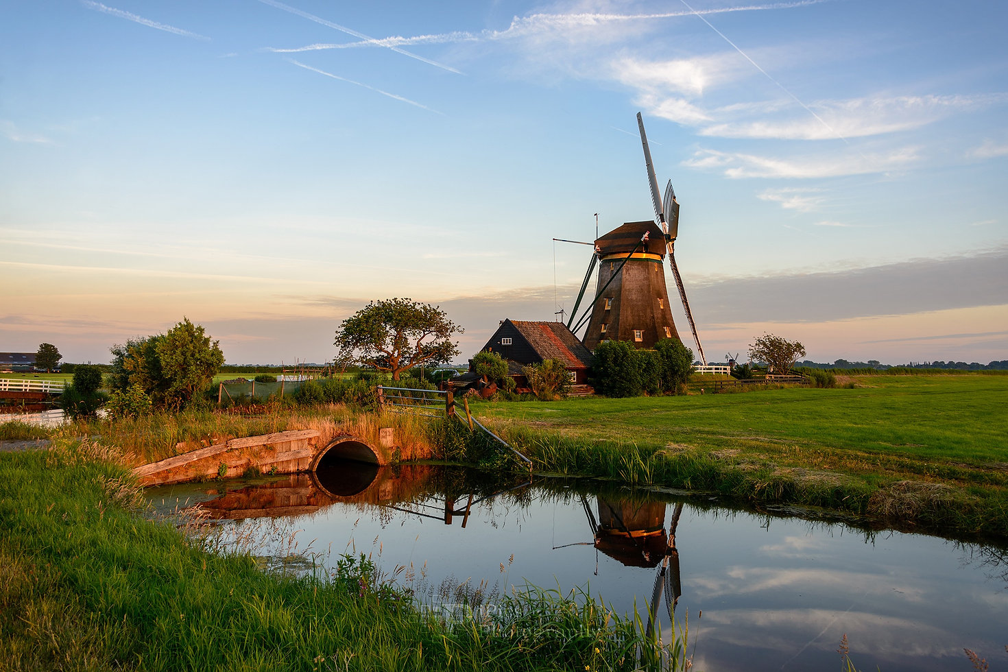 Windmill with a ditch in a landscape in