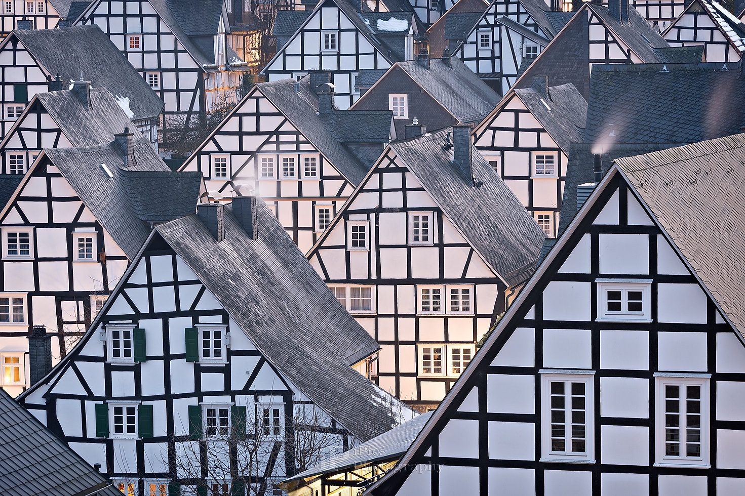 Detail of the 17th century architecture with half-timbered houses in the colors black and white with smoking chimneys and the lights on in the early evening in Alter Flecken, the city center of Freundenberg, a town close to Winterberg in North Rhine-Westphalia, Germany.